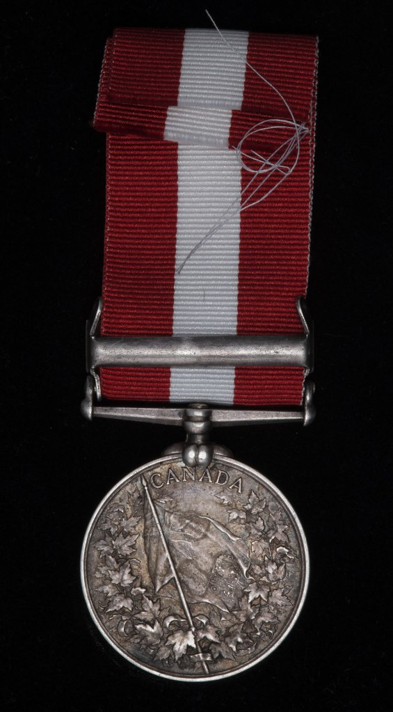 A Fenian Raid Medal with 1866 clasp (red and white ribbon)